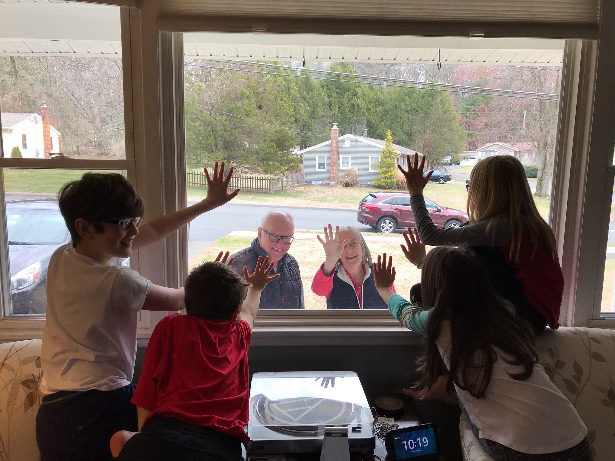 Four children with their hands on a window from the inside. Two adults wave from outside.