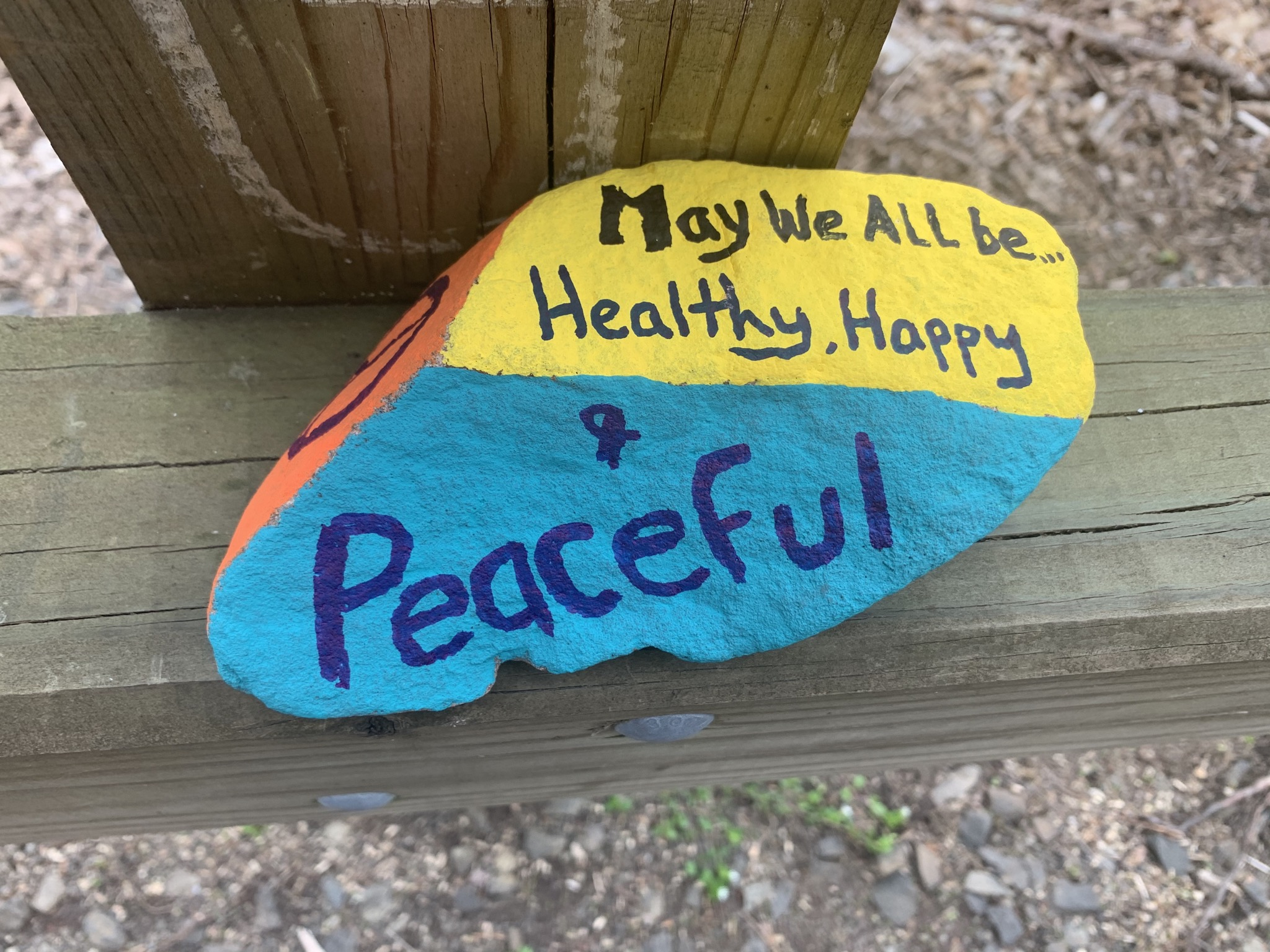 A painted rock that reads 'May we all be healthy, happy, & peaceful'