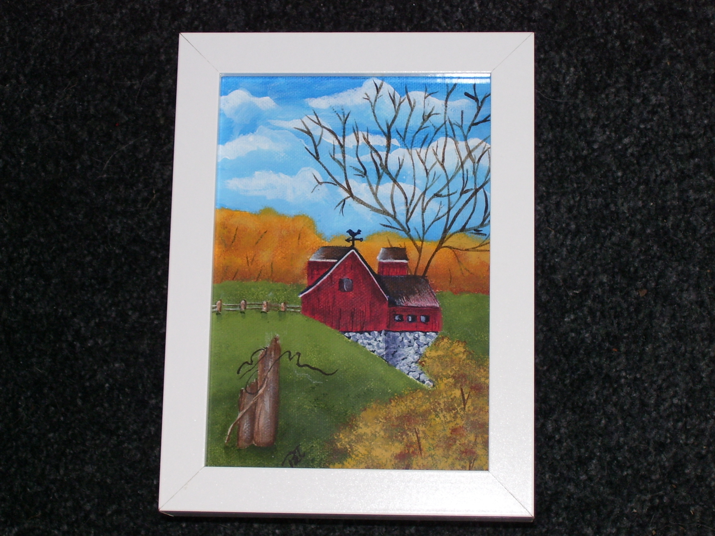 Framed painting of a red barn.