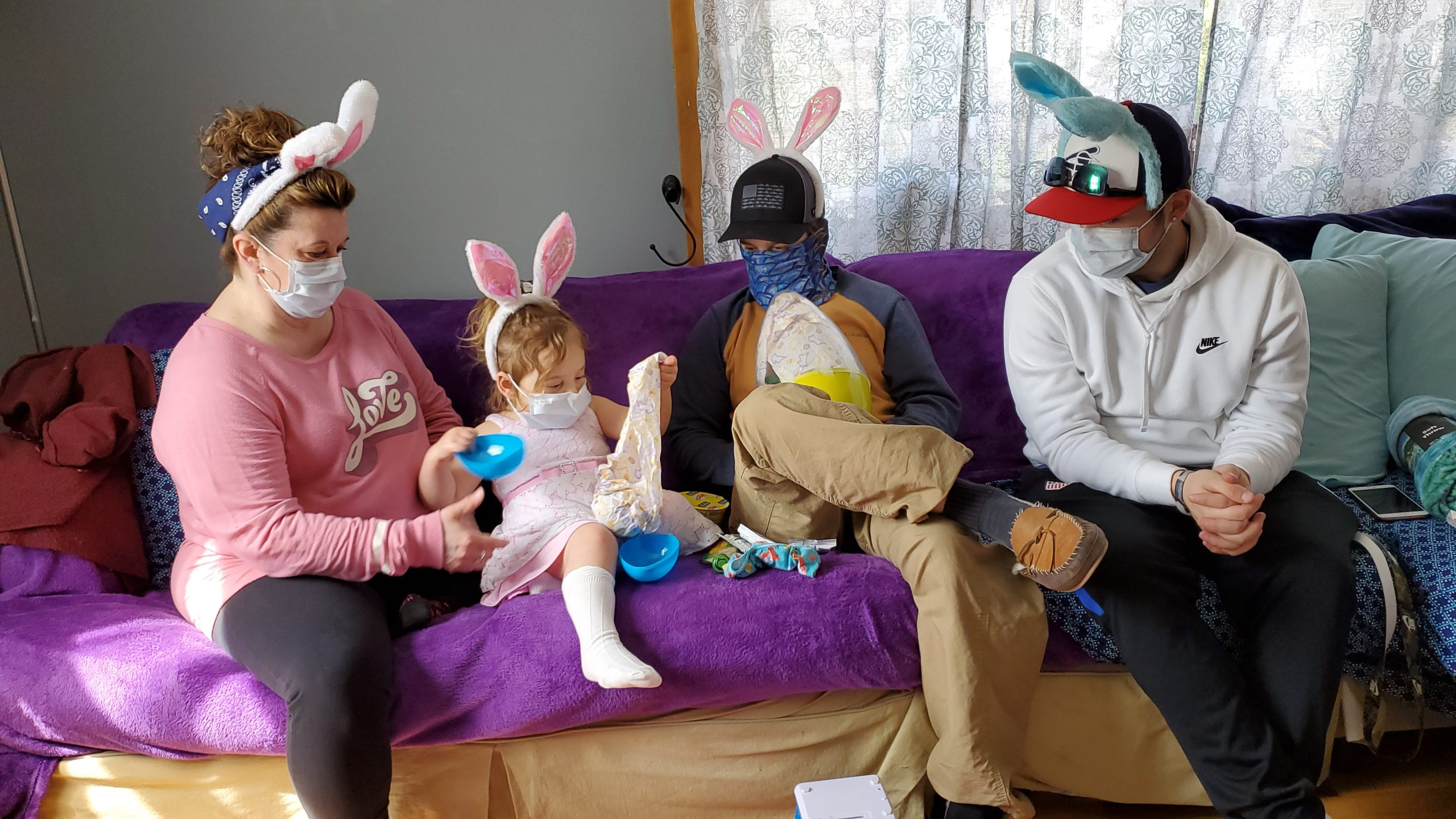 One child and three adults wearing face masks and bunny ears.
