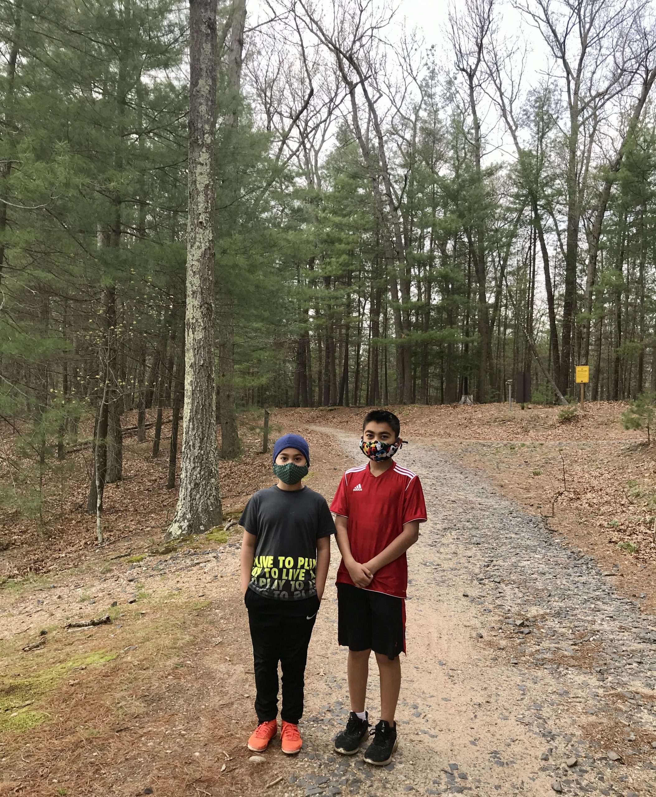 Two boys on a hiking trail, wearing face masks.