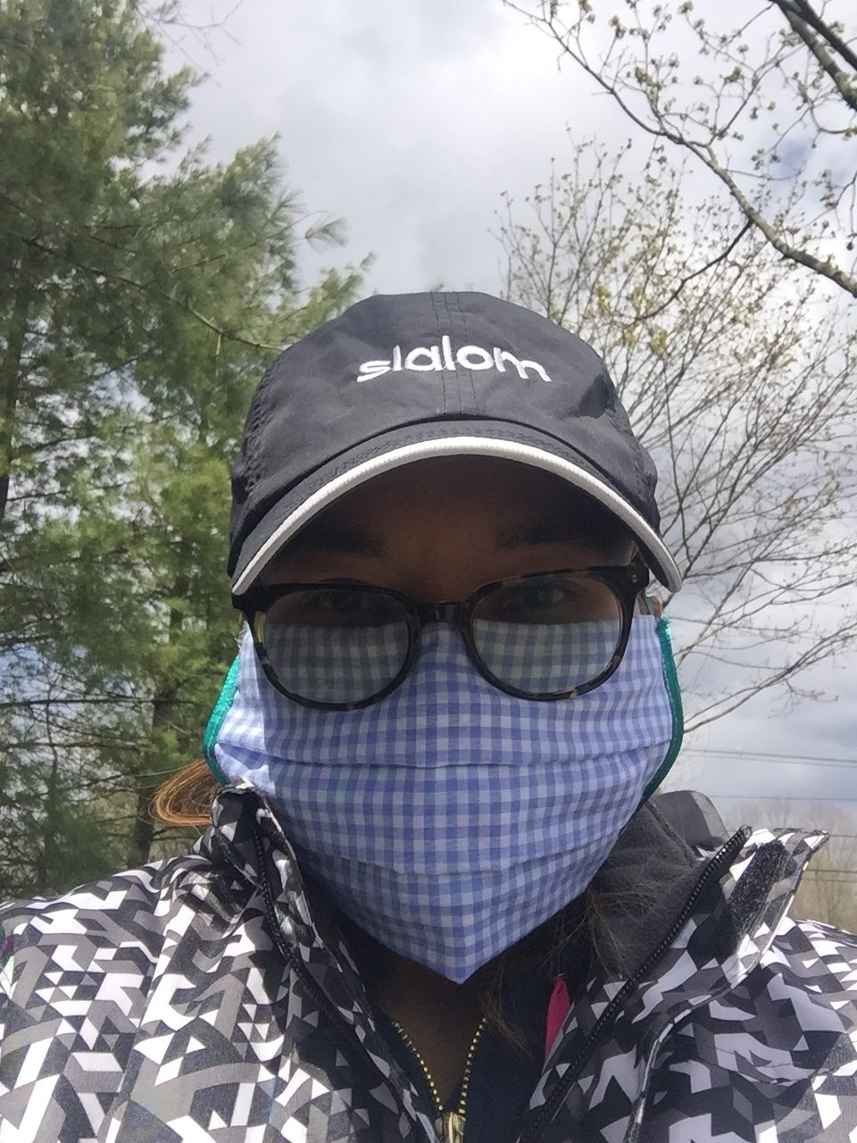 Woman with gingam face mask, glasses, and hat.